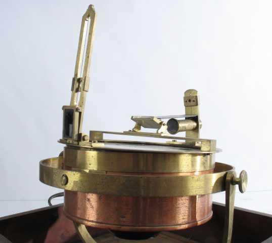 Kasse av mørk eik, i den er montert et instrument av jern og messing.