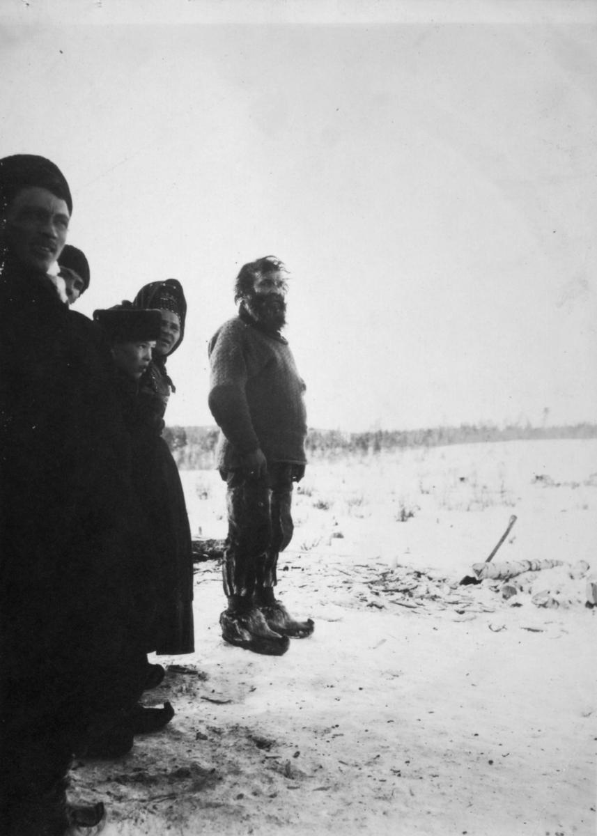 'Sunjel-skolter.' Skoltesamer i Sunjel i Murmansk fylke i Russland. Kledt i skaller og skinnbukser. En mann har på seg en strikket ullgenser.