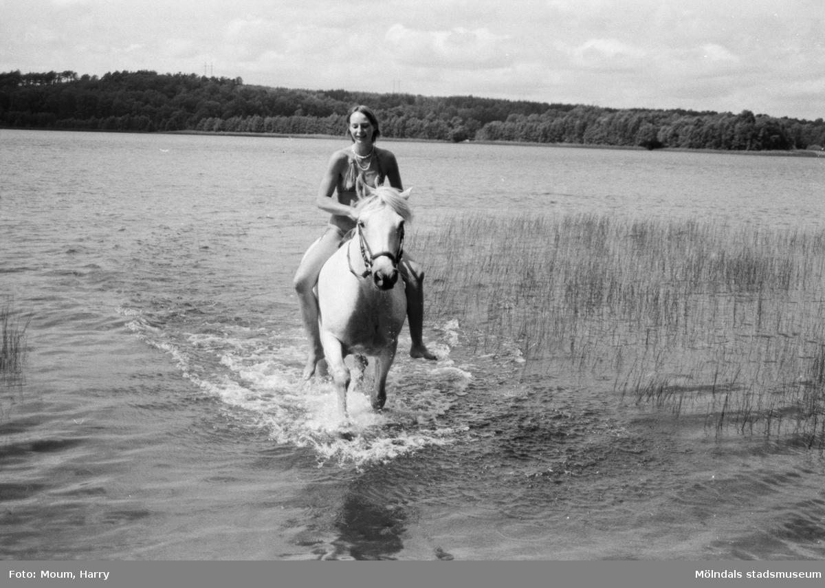 """Flicka rider på häst vid en sjö, år 1983.   """"Ridtur i sommarland  Sommar, sommar, sommar. En härlig årstid för oss alla. Behovet av svalka är stort även hos våra fyrbenta vänner. Här är det Jorunn som ser till att hennes häst Teddy får svalka.""""  Fotografi taget av Harry Moum, HUM, för publicering i Mölndals-Posten, vecka 29, år 1983."""