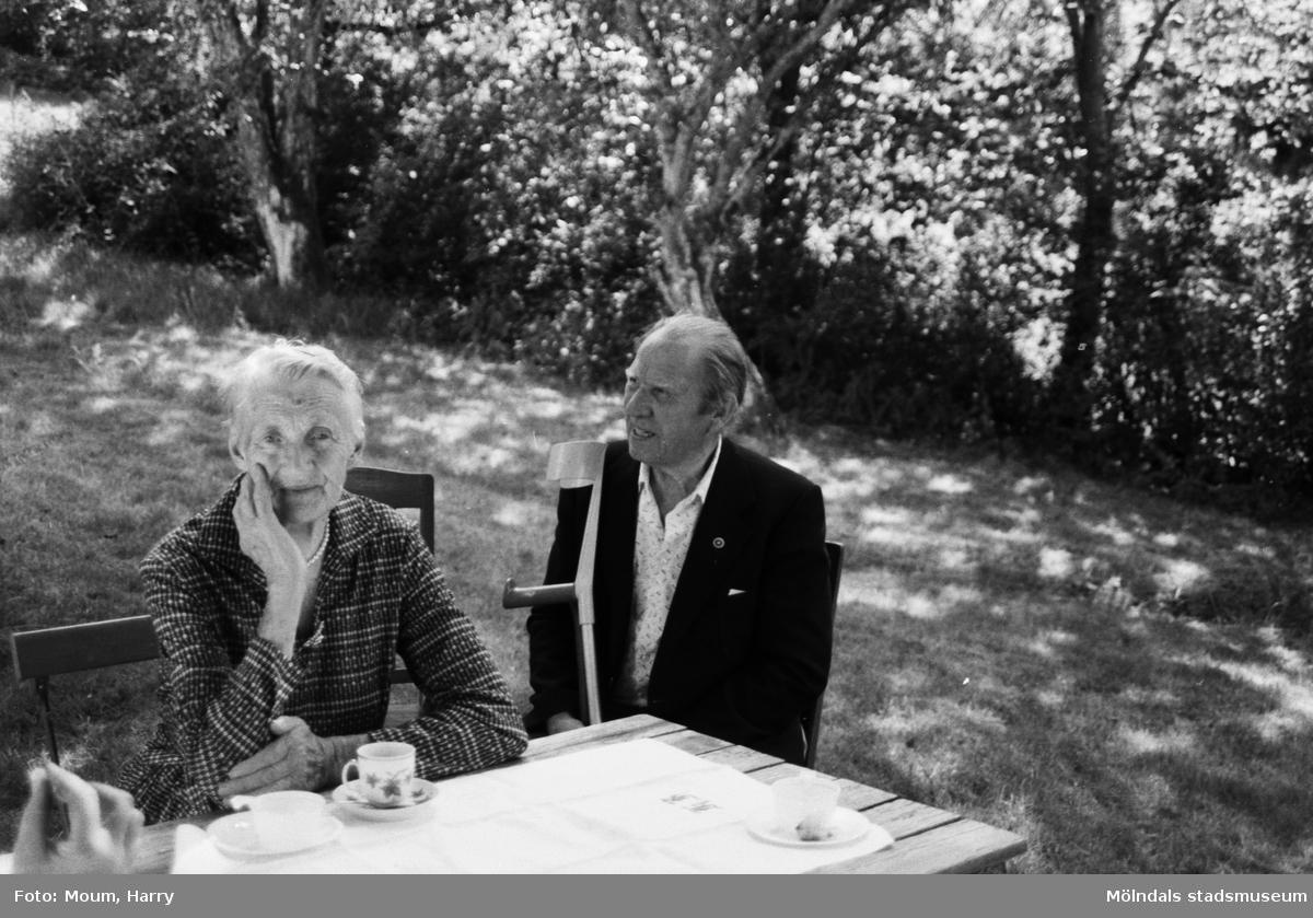 Lindome Hembygdsgille firar 20-årsjubileum på Börjesgården i Hällesåker den 23 juli år 1983. En kvinna och en man i trädgården.  För mer information om bilden se under tilläggsinformation.