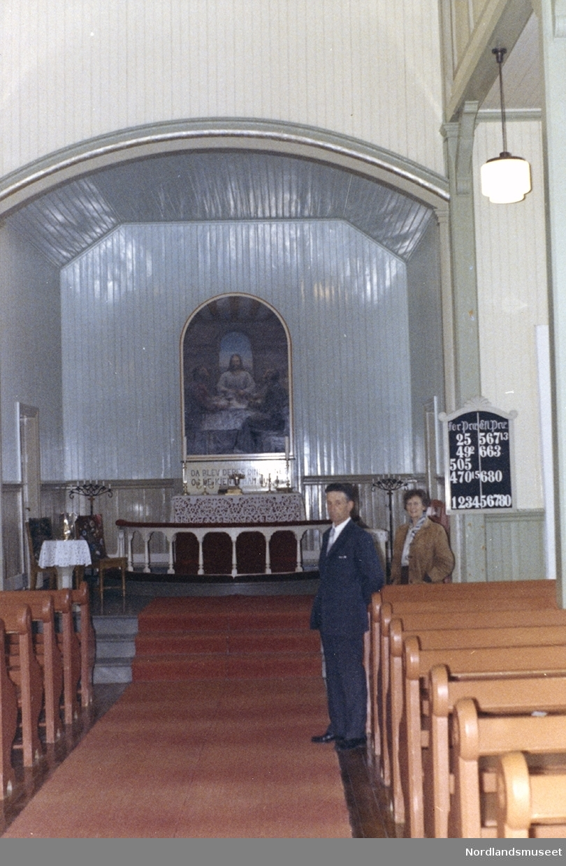 Valnesfjord kirke. Interiør. Bildet tatt i midtgangen mot alteret. 2 personer står ved midtgangen.