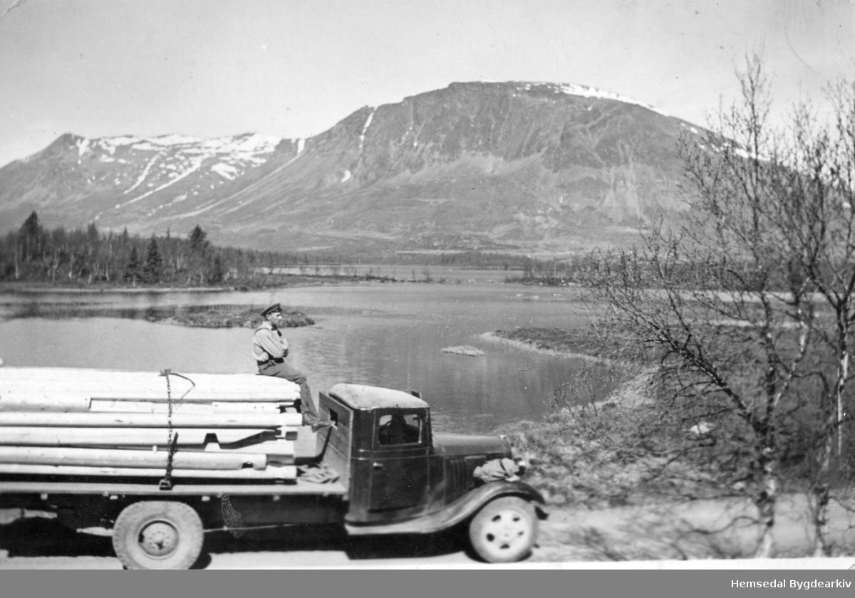 Sjåføren Trond Wøllo har teke seg ein pause på toppen av eit stort materiallass ved Hestaneåni med Helsingvatn og Skogshorn i bakgrunnen.