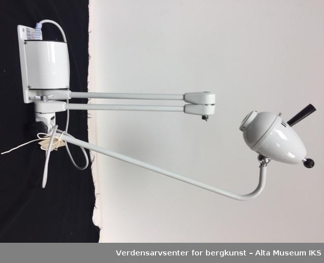 Kolbeformet hvit lampe, på et stativ med to ledd som gjør at man kan trekke lampen i ulike lengder og retninger. Det er to svarte håndtak på selve lampen. Den står på en sokkel med en ledning. Glassfronten er rund og gjennomsiktig.