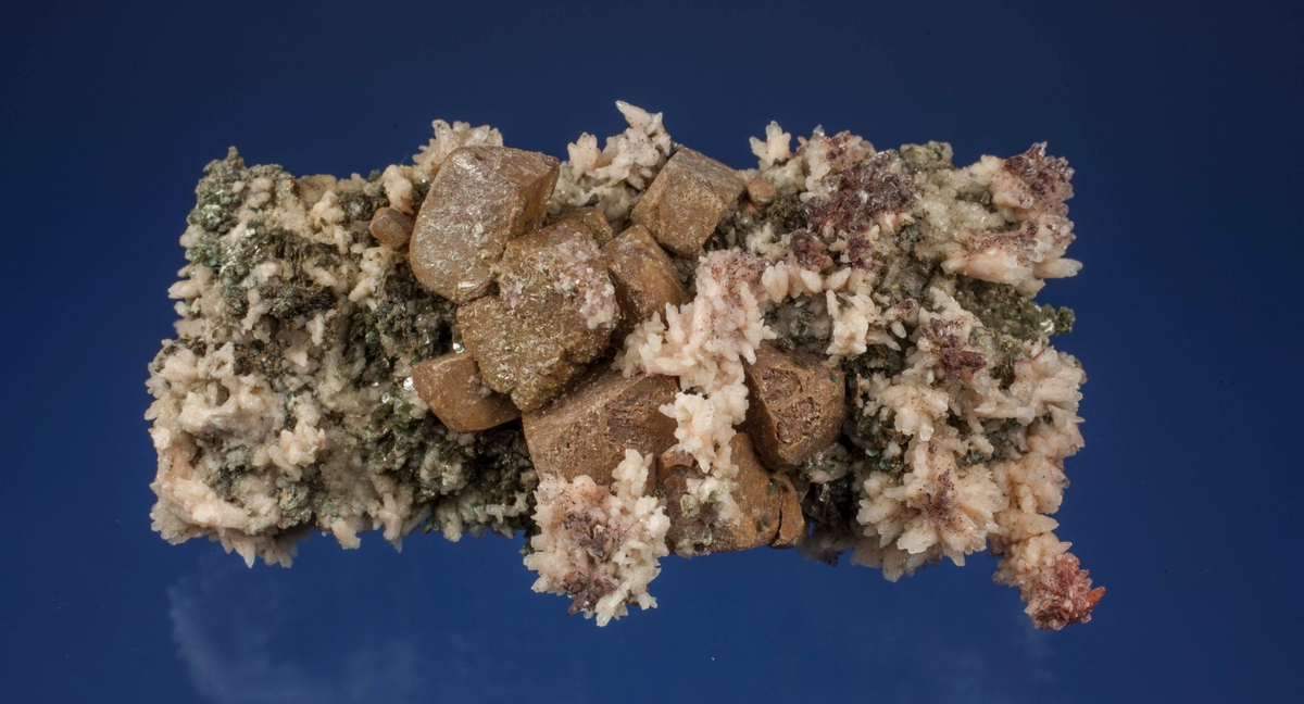Kalsitt xls med inneslutninger av pyritt xl og pyrrhotittflak, en kvarts xl, litt bergart. Kongens gruve.