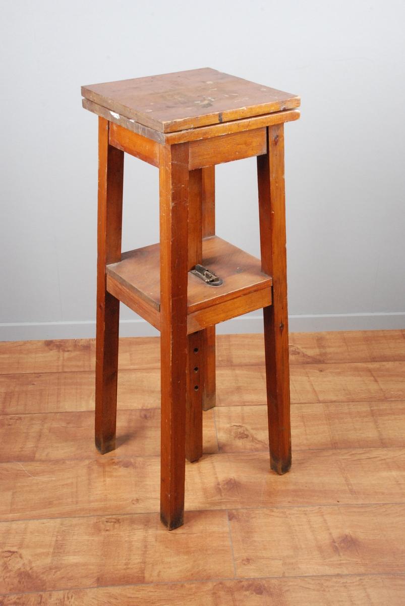 Bord med 4 ben og dobbel plate. Øverste plate er montert på en høydejusterbar stang som går ned i et hull i underste plate. På toppen av den nederste platen er det festet låsepinne for den justerbare stangen. Stangen har hull for låsepinnen.