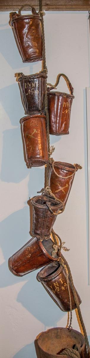 Brannbøtta er laget av to lærdeler som er sammenføyet med søm. Det er sydd inn to tre-spiler, som går fra kanten av bøtteåpningen og og ned til bunnen. Disse er plassert vis-a-vis hverandre i forhold til bøttens diameter. Trespilene fungerer antagelig som forsterkning både av bøtten og hankefestet. Bøtta er malt med rødbrun farge både utenpå, inni, og i bunnen.