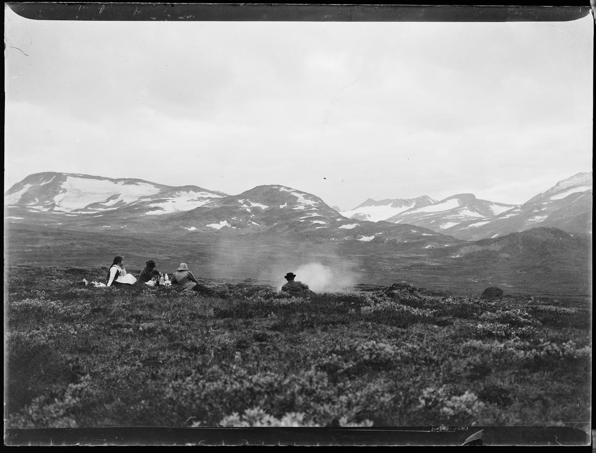 """""""Heimdalen 1906"""" (inskr eske). Fjell-landskap. Snødekte fjell i bakgrunnen. Fire personer ligger i lyngen. Det ser ut til at de har tent et bål. Alle er vendt fra kameraet."""
