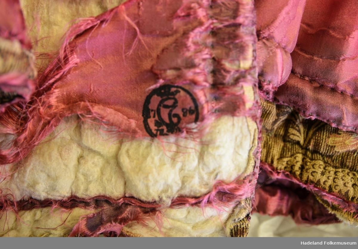 Cape kvinne med rosa liten krage. Kort modell. Silkebrokade. Vevd bomull innvendig (Kattun); bomullstrykk/silke?. Vattert med ull. Lerret innvending. Sydde kanaler på skuldrene. Stempel nederst på høyre side.