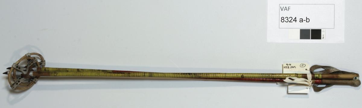 Skistaver, langrernnsstaver. Stenger (bambus) med håndfeste m/løkke ene ende, metallspiss og ring (bambus) i lærfeste (i kryss) andre ende. Spleiset med tape.  b) Lærhylse over stang m/håndfeste.