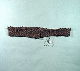 """Stickprov av växtfärgat ullgarn i två olika nyanser av brunt. Slätstickat mönster.  Remsan är förmodligen avklippt från ett plagg, antingen kjol eller kofta. Enl. Ulla Melins inventering:""""Mönstret finns avbildat i """"Gotländsk sticksöm"""" på en vante från Tofta, sid 24, nr 25."""""""