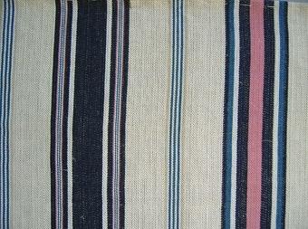 Vävprov, bolstervarsrandigt tyg i oblekt/vitt, blått och rosa, vävt i spetskypertbindning med varpeffekt.Varp i oblekt, blekt, beige, ljusblått, mörkblått och rosarött bomullsgarn nr 30/2.Inslag i oblekt tunt lingarn.