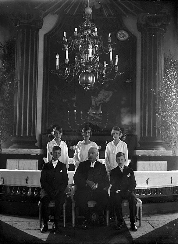 Kyrkointeriör, konfirmation, fem konfirmander och en präst.