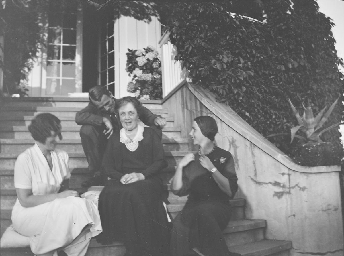 """Tre kvinner og en mann sitter på trappen opp til verandaen fra den """"Victorianske hagen"""" på Linderud Gård. De har tatt med puter som de sitter på. Verandaen er dekket av klatreplanter."""