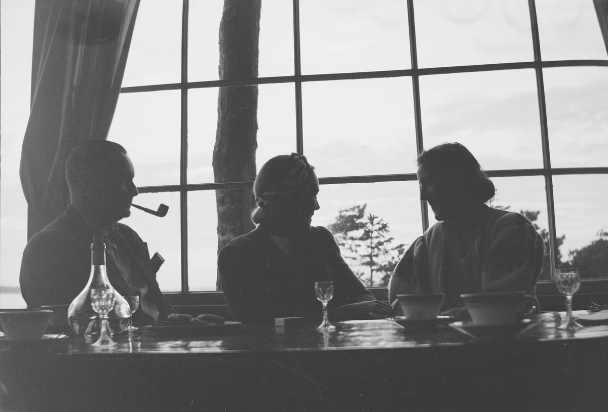 To kvinner og en mann sitter ved et bord med glass, kopper og skåler samt røkesaker. De sitter innendørs med et stort vindu i ryggen.