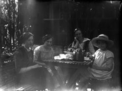 Fyra personer runt bordet, tedrickande.(Några av dem är giv
