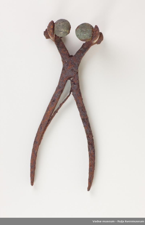 Modifisert tang i jern med lange knipehender med runde kuler i bronse på.Kanskje bronsekulene er fra hestens dombjeller? Antatt brukt til kastering eller ved slakting av kyr.