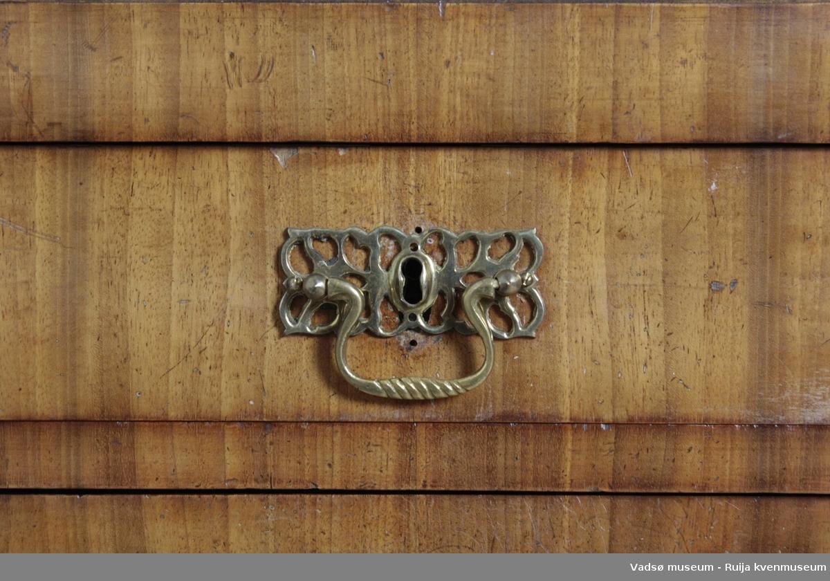 Kommode av mahongy-finer. 4 skuffer, hvorav den øverste er noe smalere enn de øvrige. Messing håndtak med beslag med gjennombrutt mønster. Avrundete hjørner på forsiden. Lave, dreide ben med en liten kloss øverst.