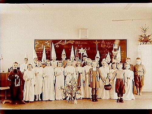 Praktiska Mellanskolan (Olaus Petriskolan), Lucia med tärnor och stjärngossar, klass 1, 26 skolbarn med lärarinna fröken Olsson.