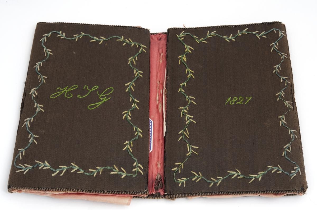 En brodert lommebok. Påbrodert H. J. G. - 1827, grønn silke, broderte blomster med rødt for. Efter Hans Jacob Grøgaard.