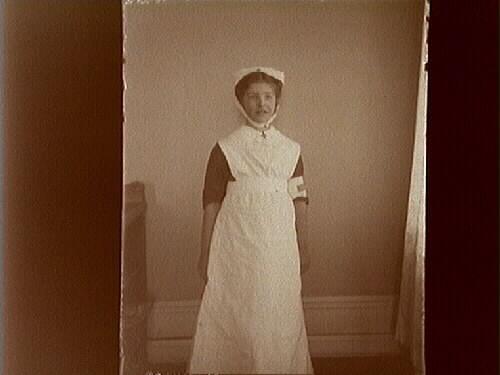 Sjuksköterskeklädd flicka.Maj Thermaenius leker, som ofta, sjuksköterska.
