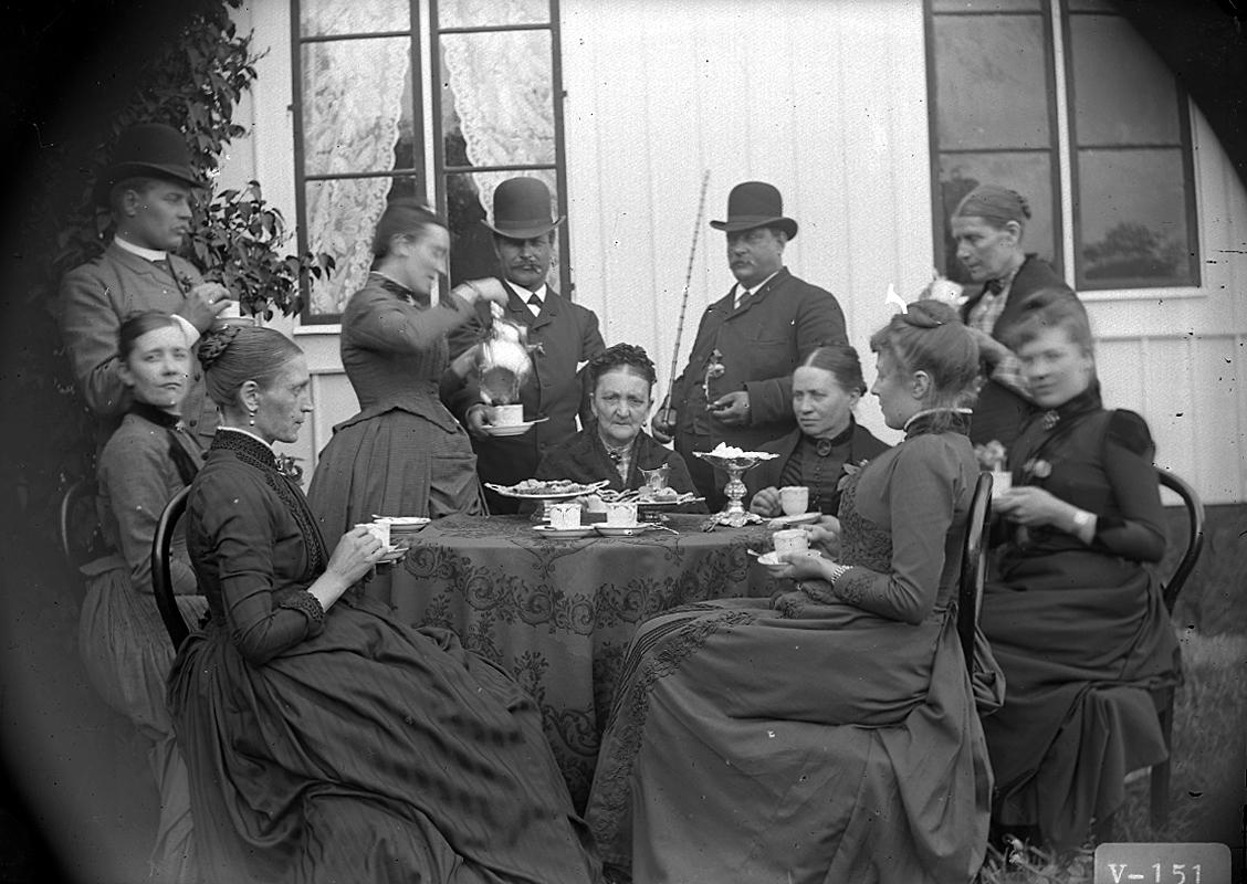 Grupp elva personer vid kaffebordet. Bostadshus i bakgrunden.