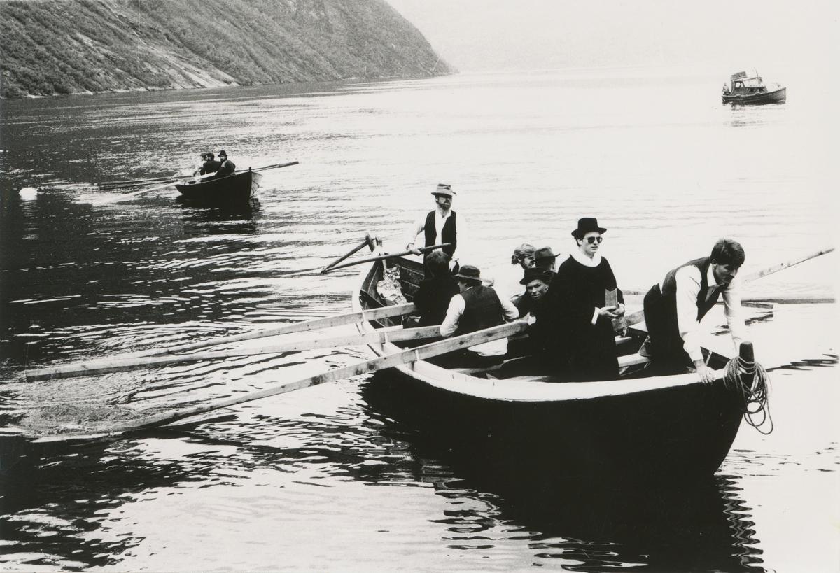 Mennesker med klær fra gamledager i robåt på fjorden. Fra Storfjordens Venner sitt sommerstemne i Syltavika.
