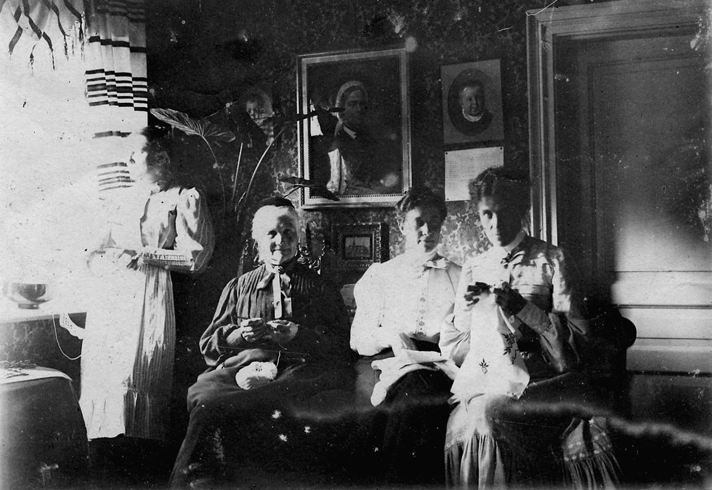 Rumsinteriör, fyra kvinnor. Broderi, virkning, m.m.Från vänster: 1. Juliana Mannerfeldt, född Lagerholm (dotter till Wilhemina Lagerholms bror Per Didrik Lagerholm och Juliana Christina Lagerholm, född Åstrand).2. Wilhelmina Lagerholm (faster och moster till de övriga på bilden)3. Helena Bastholm, gift Åkerblad.4. Elisabeth Bastholm.Helena och Elisabeth Bastholm är döttrar till: Kykoherde Johan Bastholm (1816-1892) och Ingeborg Elisabeth Hildegard Bastholm (1830-1897), född Lagerholm. (Ingeborg var Wilhelmina Lagerholms syster).
