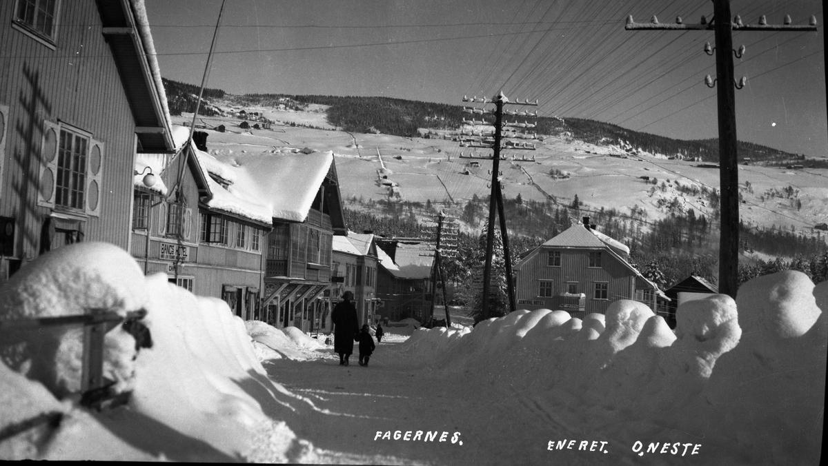 """""""Frenning-Haugene-gården"""", Gullhagen-gården, Elvely hotell og Central hotell, langs snødekt gate på Fagernes. Mennesker gående i gata, Ranheimsbygda i bakgrunnen"""