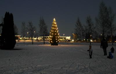 Juletreet er tent og står og lyser i mørket
