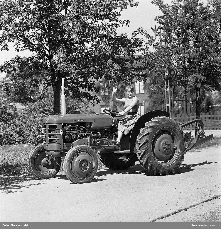 Två unga kvinnor visar upp en liten jordbrukstraktor, Volvo Krabat,  på Parkgatan. På en av bilderna skymtar den numera rivna fastigheten på Parkgatan 4.