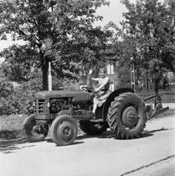 Två unga kvinnor visar upp en liten jordbrukstraktor, Volvo