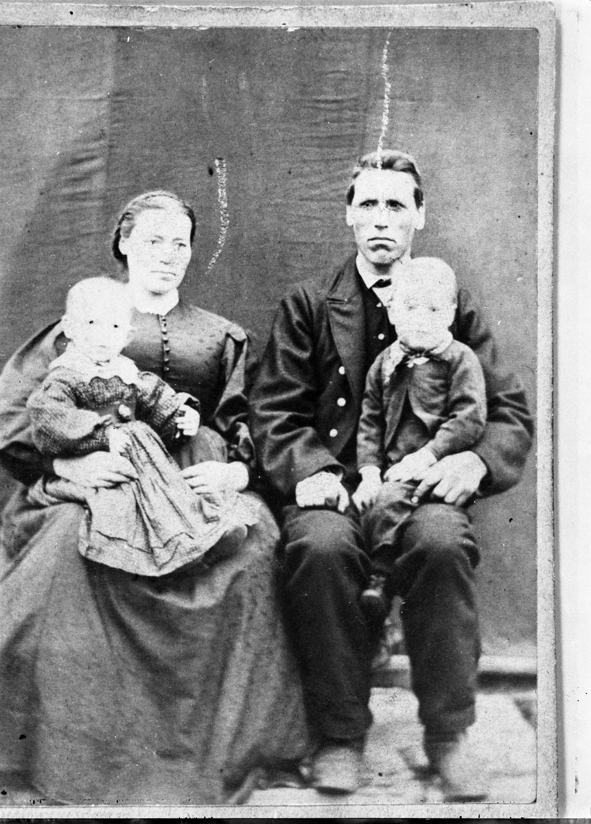 Sitande mann og kvinne med kvart sitt born på fanget