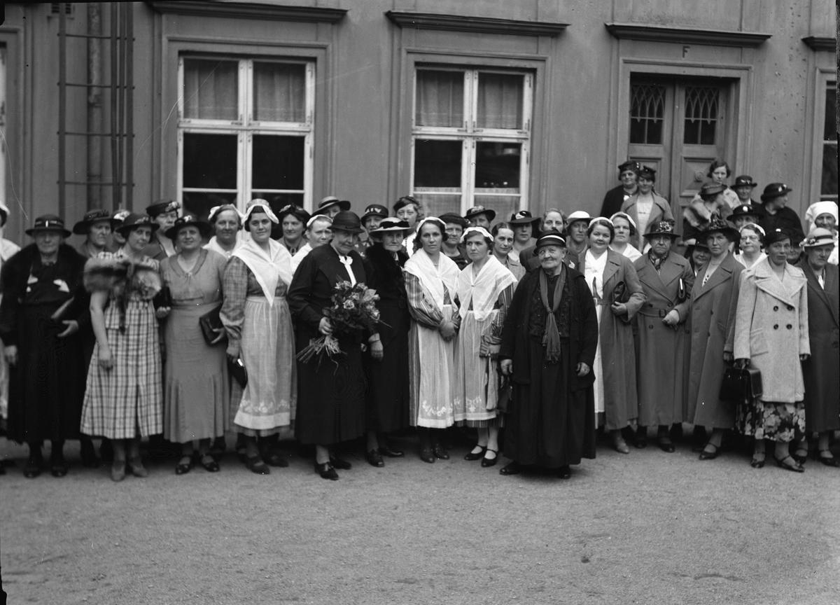 Grupporträtt med föreståndare Anna Schenström utanför Fackskolan för huslig ekonomi, Trädgårdsgatan 14, på Uppsala Läns Husmodersförbunds studiedag