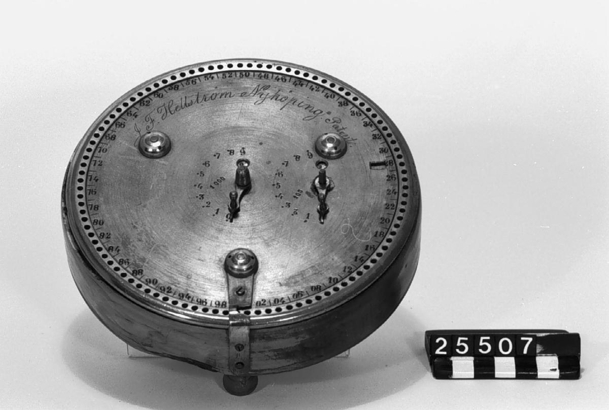 Räkneapparat för addition intill 10.000. I dosa av trä med fyra fötter, varav en kortare. Märkt: J.F. Hellström, Nyköping, Patent.
