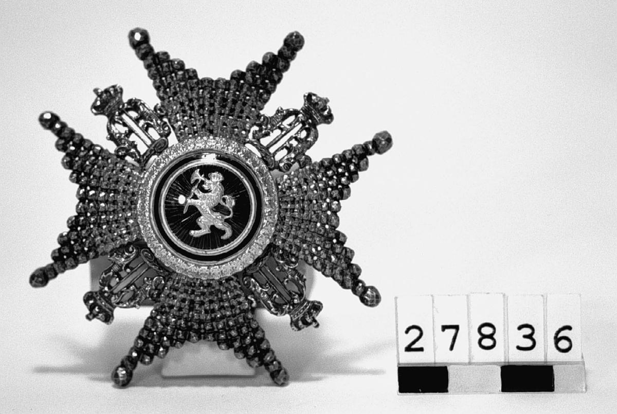 Kommendörstecken av 2. klass, i silver, av norska St. Olavs orden. 4-armat malteserkors, Oscar II:s namnchiffer emellan, förgyllt lejon på röd emalj inom vit-blå-vit ram och förgylld reliefram.