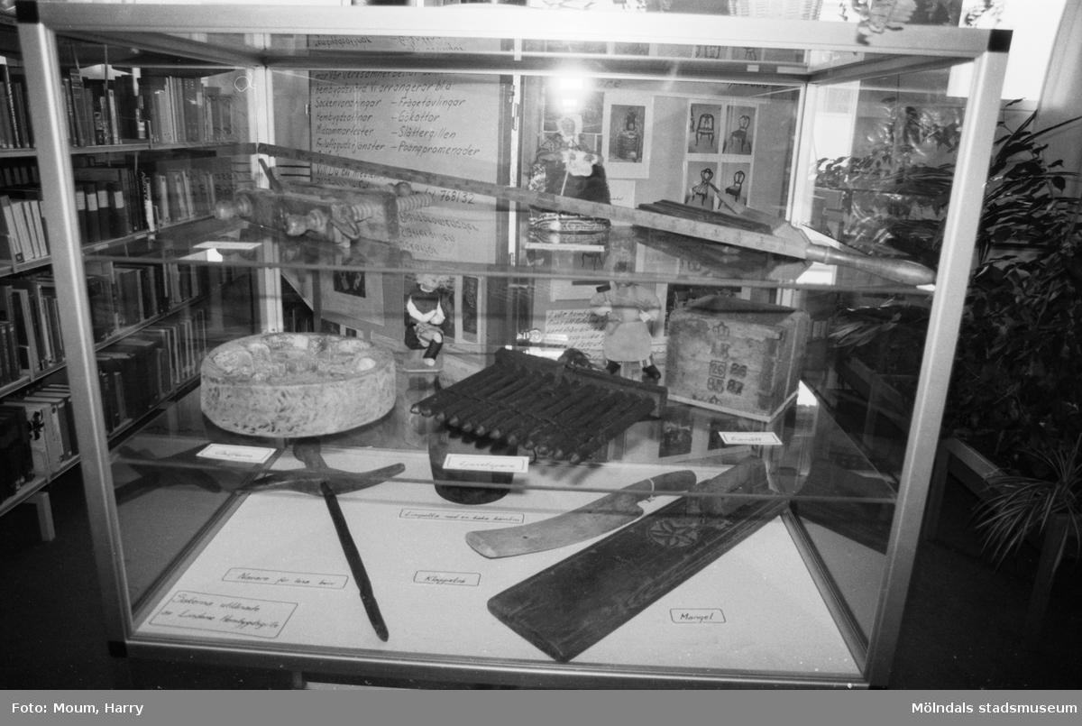 """Lindome hembygdsgille ställer ut föremål och fotografier i Lindome bibliotek, år 1984. """"Gamla föremål visas på utställningen.""""  För mer information om bilden se under tilläggsinformation."""