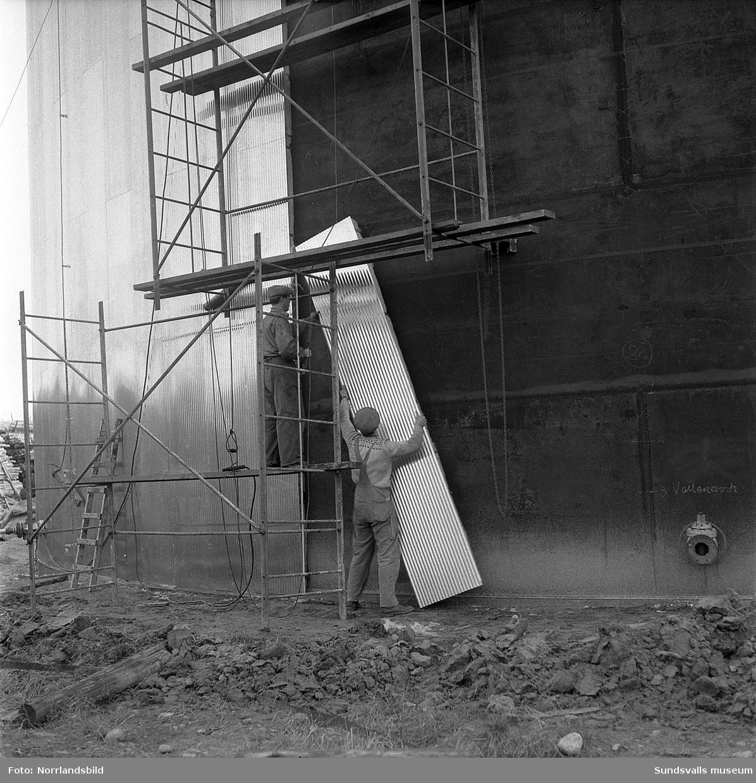 Bildserie som visar hur en cistern på Östrand isoleras och kläs in med plåt. Fotograferat för direktör Fridolf Brunnzell, Lindgrens järn.