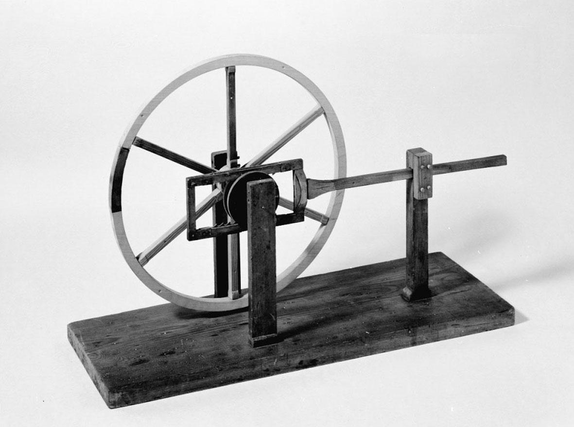 Modell ur Polhems mekaniska alfabet. Genom en fram- och återgående rörelse hos armen erhålles en kontinuerlig rotationsrörelse hos hjulet med hjälp av två fjäderbelastade kuggstänger i bygeln.