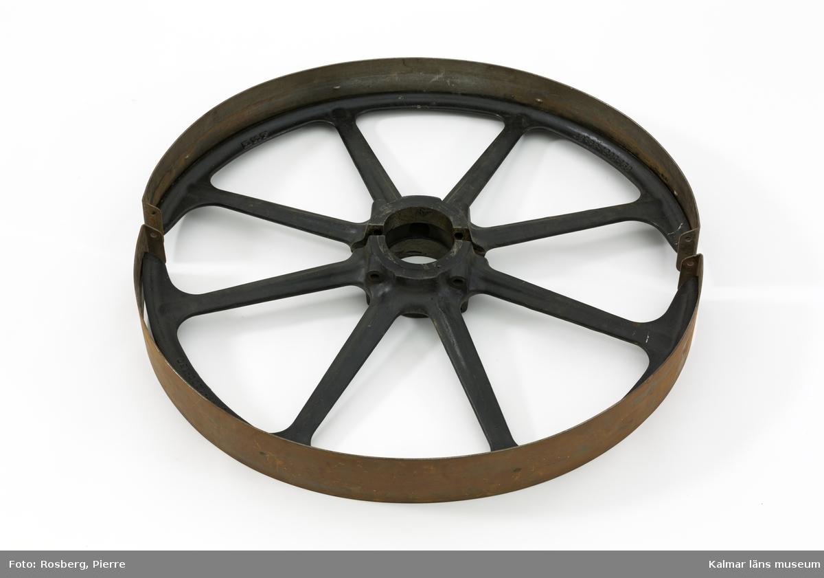 """KLM 45520:1:1-4. Drivhjul, fyra delar. Hjul av svartmålat järn, gjuten i två halvor (:1-:2). Hjulet har åtta ekrar och vid navet hål för att skruva samman de två halvorna. Båda halvorna märkta: SKF samt 48""""-PR-1200-150 på yttre ringen. Inre ringen är märkt: MADE IN SWEDEN FABRIQUE EN SUEDE. Hjulets yttre kant har en skåra för fastgöring av ett remband av stål (:3-:4), även detta i två halvor. Halvorna är märkta PB-1200-140, 48"""" 5 ½ och MADE IN SWEDEN FABRIQUE EN SUEDE.  På rembandet snurrade drivremmen. Bultar för hopmontering av delarna saknas. Drivhjulet har ingått i ett större maskineri för utformning av stavar till laggkärl."""