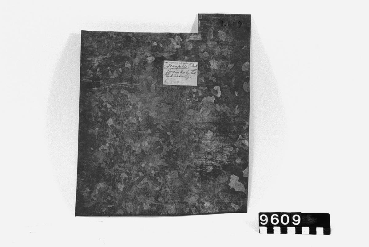 """Prov på galvaniserad järnplåt till taktäckning. Blyerts: """"Förzinkadt jernbleck till takplåt"""". M-a-6 (L-a-9). Tjocklek: c.a. 0,8 mm."""