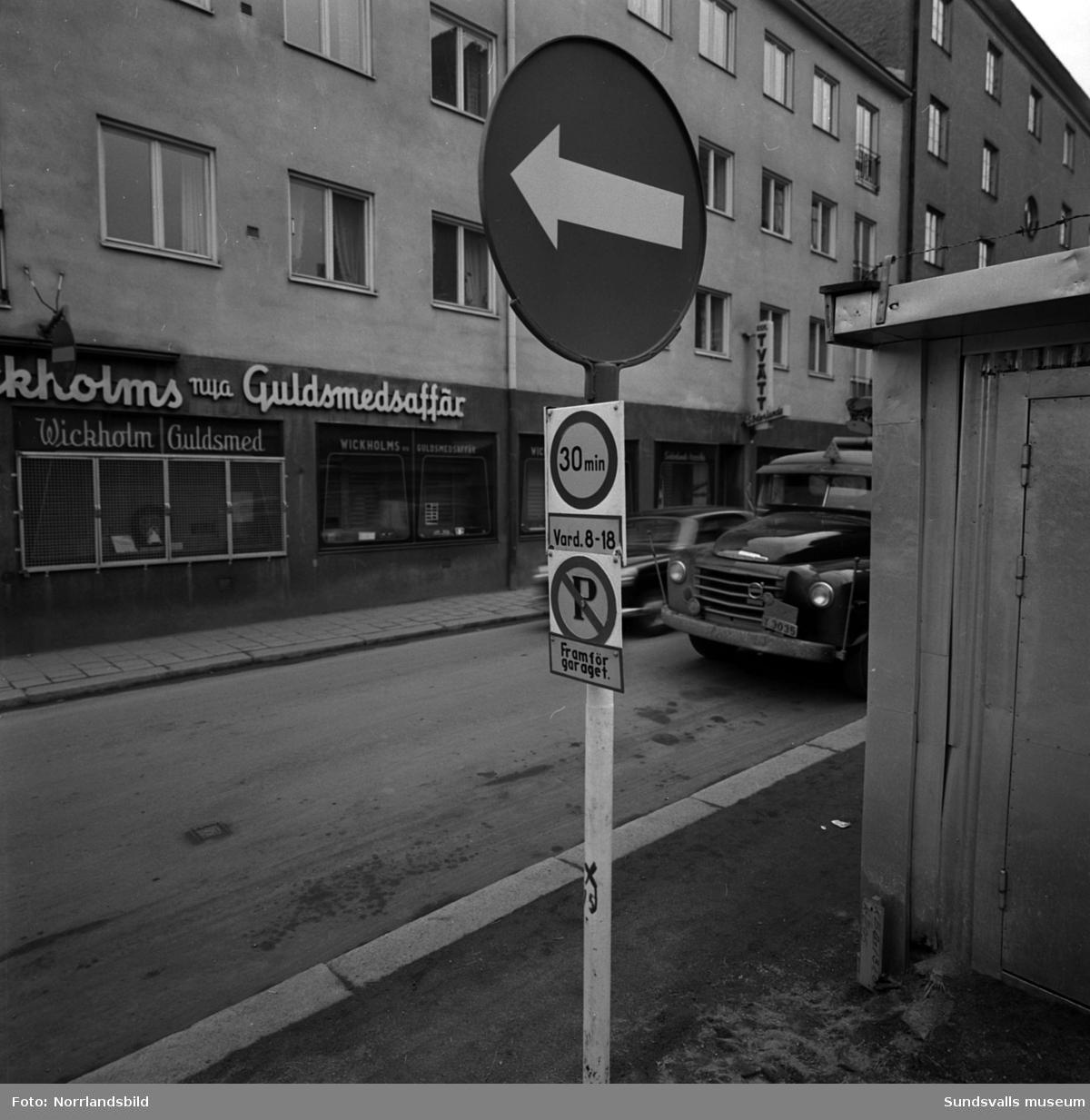 Vägskylt med mycket information på samma stolpe. I bakgrunden Wickholms guldsmedsaffär i korsningen Trädgårdsgatan-Nybrogatan.