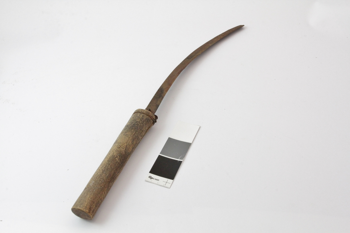 Kniv - lauvekniv? - der knivbladet er laget av et gammelt ljåblad, altså svakt buet med tykk kant på den ene siden. Ljåbladet er plugget inn i treskaftet med hjelp av noen jernspikre. Sprekk i treskaftet, derfor surret ståltråd på utsiden i kanten for å holde det på plass. Skaftet er rett og ovalt i tverrsnitt.