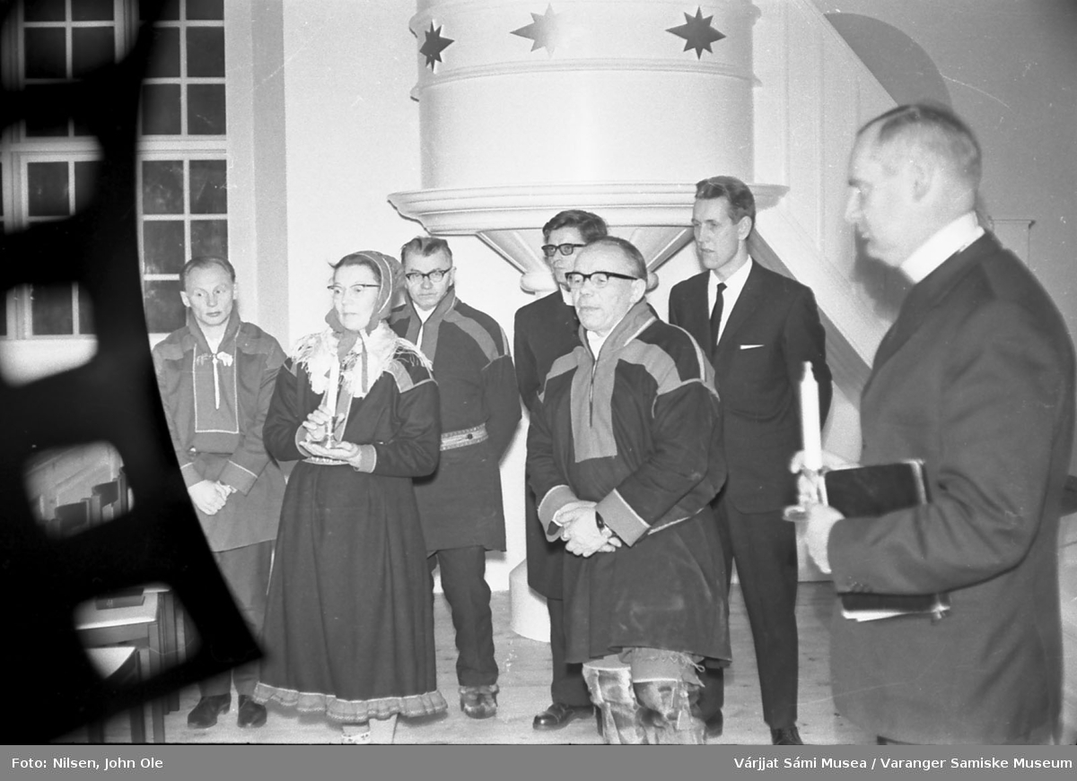 Gruppebilde inne i en kirke. Prekestol i bakgrunnen. Kvinnen med kofte og talgelys i hånden er Signe Nilsen, mens presten helt til høyre er Erik Schytte Blix. Ukjent sted høsten 1966.