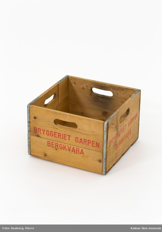 KLM 45619:31. Drickaback, trä, metall. Rektangulär träback med ribbor i botten, fyra handtag och galvaniserade metallband runt kanterna. Tryckt text i röd färg på sidorna: BRYGGERIET GARPEN BERGKVARA.