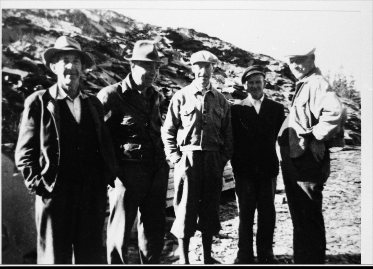 Fem menn fotografert foran en steintipp, sannynligvis i forbindelse med Valdres Skiferbrud. Alle mennene er iført hatt eller lue og en av mennene er iført en nikkers.