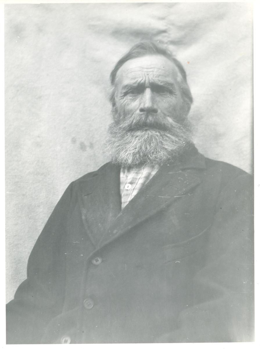 Portrett av mann i halvfigur. Han er kledd i rutete skjorte og dressjakke og har skjegg.