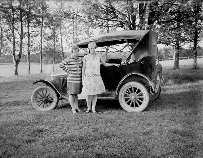 Svea Lund och Hulda Juliusson, Hedekas, framför en bil