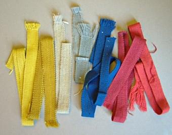 Sju stycken prover på vävda slipsband i ull. Enfärgade band vävda i rips, svagt randiga genom olika nyanser i varpgarnet. Varp och inslag i kulört och naturfärgat ullgarn. WLHF-0374:4 Grå och ljusblå varp. Tre prover, två stycken med blått inslag, ett med grått inslag. Dubbletter finns fästade på kartong numrerade 1683-1689.