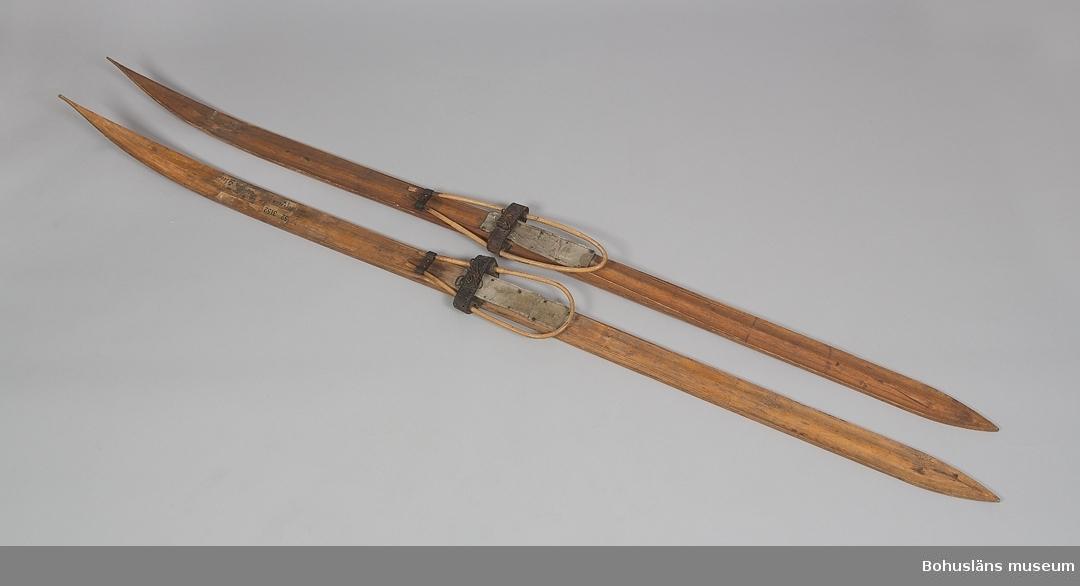 Skidor, par, lövträ - troligen björk; längd 231 cm, spetsiga i båda ändar, uppbyggd vulst i mitten; enklare ristning som dekor, tunn ytbehandling; i bindslen järn, rotting, läder och linoleummatteliknande material som fotplatta. Påklistrade pappersetiketter att den varit med om tågresa/-resor Rättvik kan skymtas, Uddevalla i flera tappningar.
