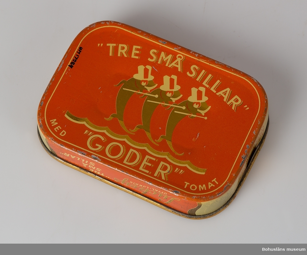 """Röd och gul rektangulär tom burk med gulddekor.  Text på lock och botten: """"Tre små sillar"""" med """"Goder tomat"""". På sidan """"Luckeys, uttal: lukäjs, """"Tre små sillar."""" Innehåll 100 gr. AB Elis Luckeys Konservfabrik Lysekil-Sweden."""" Öppnas med nyckel. Se UM017232"""